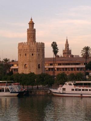 Kaksi tornia : vasemmalla Torre del Oro (kultainen torni) Almohad dynastian kaudelta 1200-luvun alusta ja oikealla Sevillan katedraalin Giralda kellotorni joka on entinen moskeijan minareetti. Giraldan yläosa on renessanssityylinen. Edessä Guadalquivir joki, jonka vartiaksi kultainen torni rakennettiin.